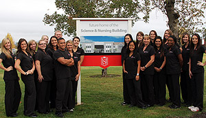 A group of nursing students pose for a picture where the Science and Nursing Center will be constructed