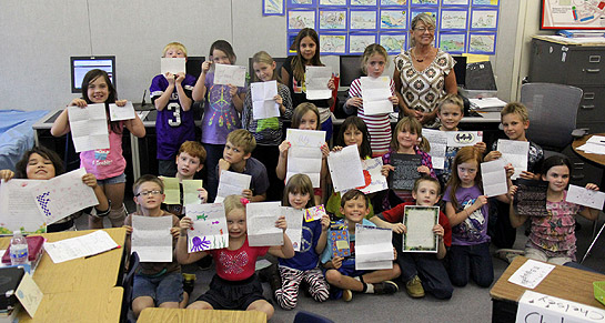 Karen Lawrence's class at Juniper School holds up letters received from Simpson University pen pals