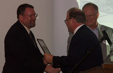 Dave Meurer presents Dr. Robin Dummer with a plaque, while Brad Williams looks on