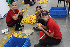 Simpson University softball players help put stickers on ducks for the derby