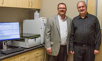 Drs. Robin Dummer and Brian Hooker stand next to Simpson University's new ion chromatograph