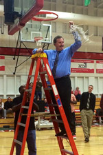 Head men's basketball coach, Jim Holcomb, cuts down the net after the Red Hawks' victory