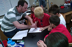 Biology professor Trent Smith gives a lesson on DNA to Juniper School students visiting campus
