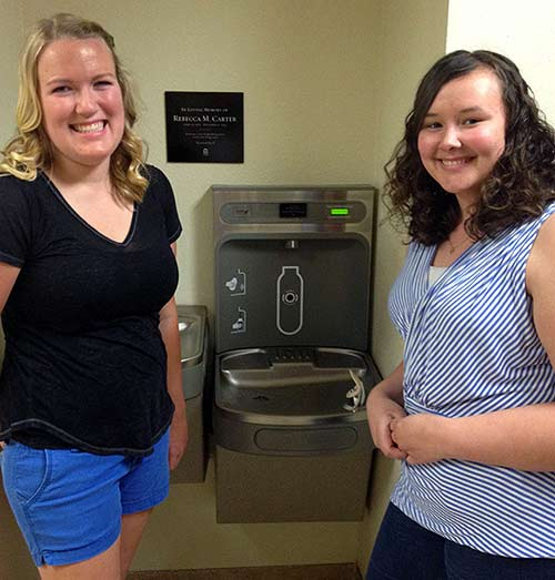 Two Simpson University seniors Lord stand by a new water-filling station, dedicated to professor Rebecca Carter, in the Owen Student Services Center